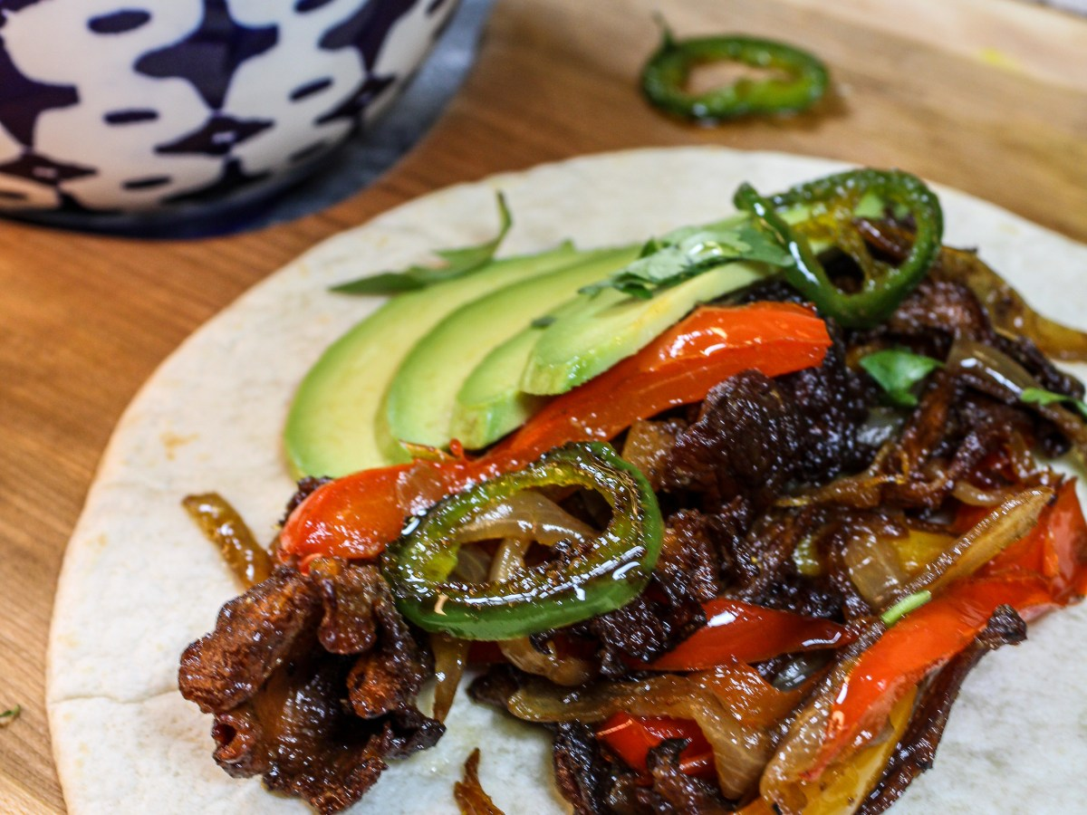 Vegan fajita filling with mushrooms, peppers, avocados and onions on a small tortilla