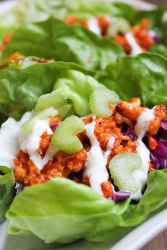 Buffalo cauliflower inside green leaf lettuce wraps. Garnished with a drizzle of ranch dressing and sliced celery.
