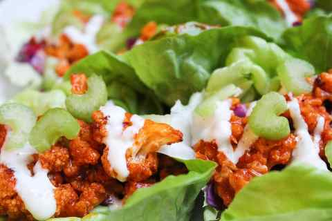 Picture of several green lettuce leaves filled with crispy orange buffalo cauliflower with a drizzle of white ranch dressing.