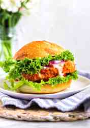 Picture of a buffalo cauliflower sandwich with lettuce, tomato, and ranch dressing between a vegan bun.