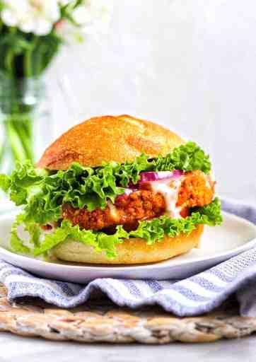 Buffalo cauliflower with lettuce, tomato, red onion, and vegan ranch between a vegan bun.