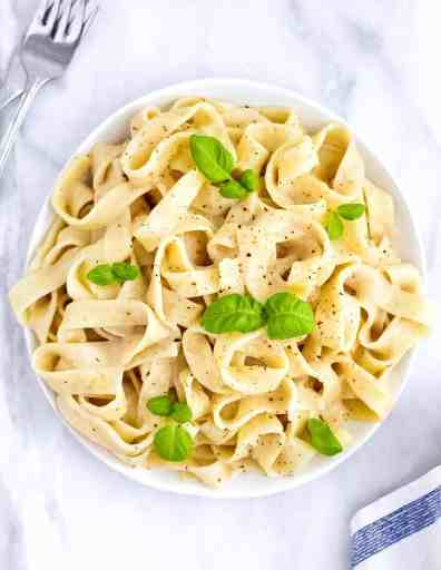 Picture of lemon pasta in a white dish garnished by green basil leaves.