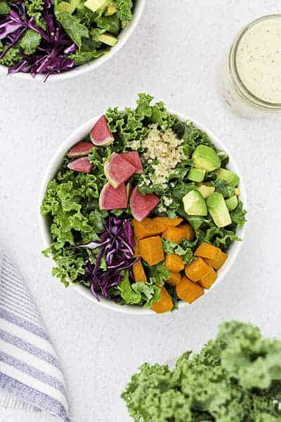 A power bowl with kale, sweet potatoes, radishes, avocado, and quinoa.