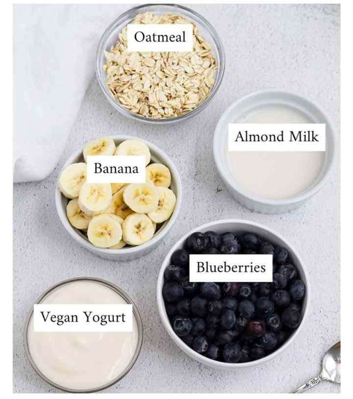 Picture of small clear and white bowls filled with oats, sliced bananas, blueberries, yogurt, and almond milk.