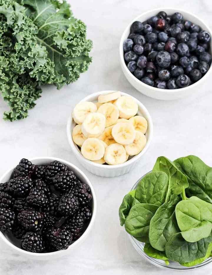Smoothie ingredients in separate bowls, pictured is a bunch of kale, blueberries, blackberries, bananas, and spinach.