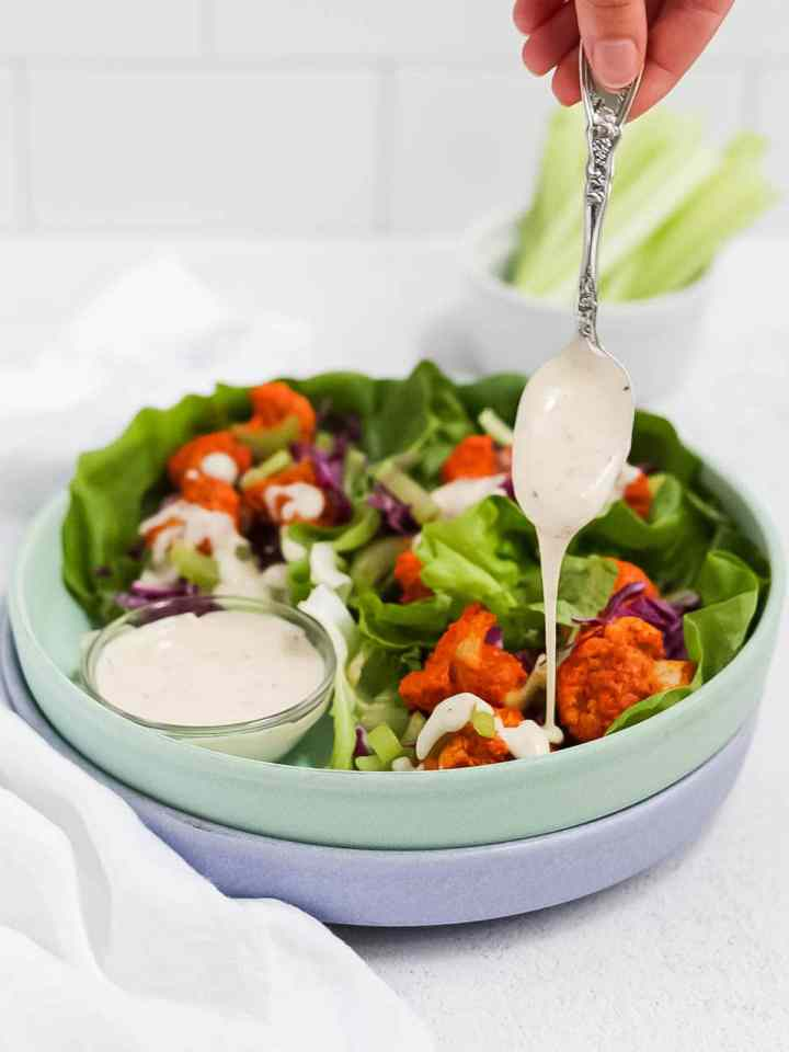 Picture of 3 buffalo cauliflower lettuce wraps with a spoon drizzling ranch on top of one of the wraps.