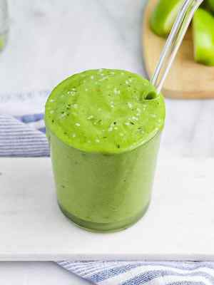 Picture of a clear glass filled with a bright green smoothie. Topped with hemp seeds and has a glass straw in the cup.