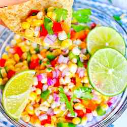 Tortilla chip scooping up corn salsa out of a bowl.