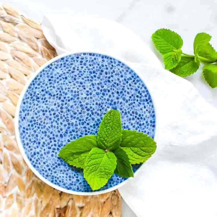 Blue spirulina chia seed pudding in a white bowl, garnished with fresh sprigs of green mint