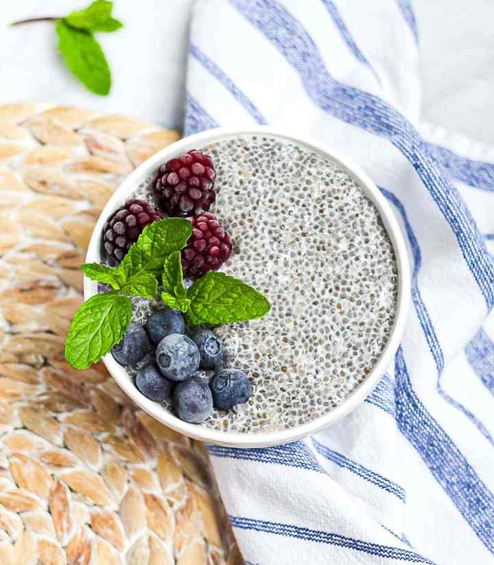 Chia seed pudding in a white bowl garnished with berries and fresh mint sprigs.