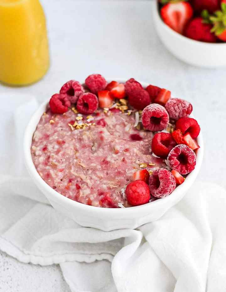 Finished picture of pink raspberry oatmeal, garnished with raspberries, strawberries, and granola.