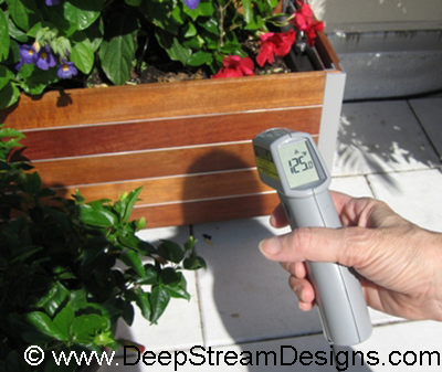 Woman with thermal gun taking the skin temperature of a planter on a Miami roof deck showing 125 degrees