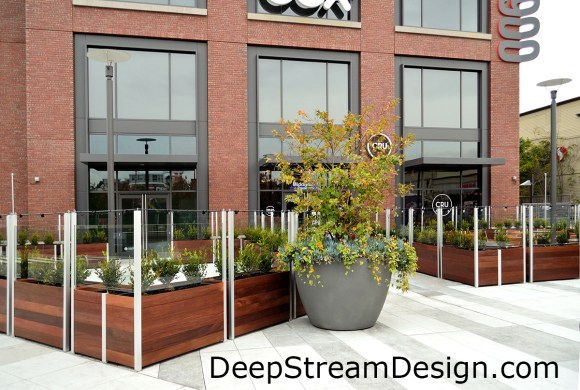 Stand alone individual Commercial Wood Planters anchor glass screen wall create a warm, inviting, upscale outdoor dining area by creating a windbreak and providing a mounting location for lighting. Click for info