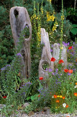 natural driftwood sculpture in cottage style planting