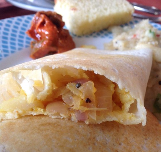 Traditional Indian breakfast of rice dosa filled with a spiced potato, onion mixture