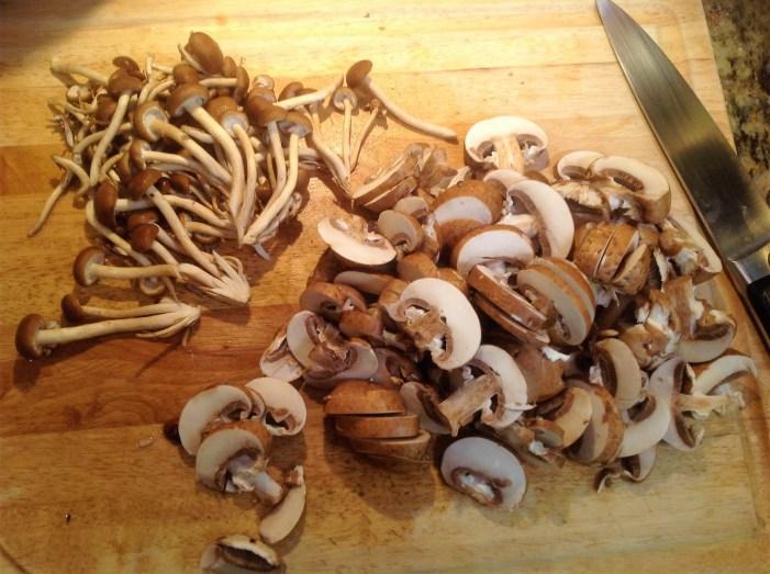 Use a knife to slice cremini, white button, and Portobello mushrooms
