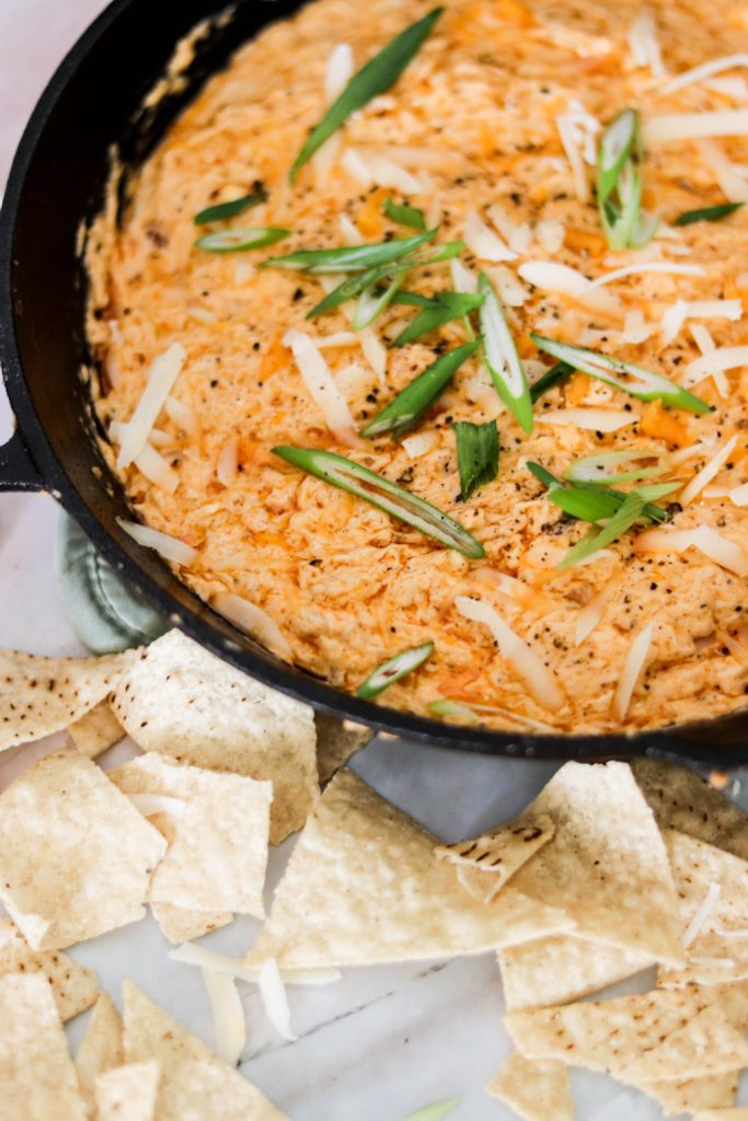 Photo of baked buffalo crab dip topped with green onions and extra parmesan cheese.