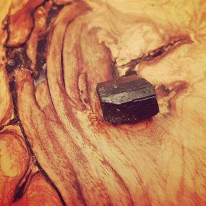 Black tourmaline crystal on wood background