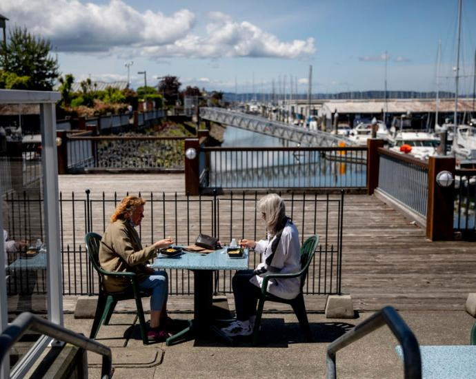 Leann Durnil, left, and Mary Buck, both of Everett, have their takeout lunch together on the patio of Lombardi's Italian Restaurant in Everett on June 3, 2020.