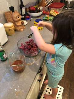 Child pouring sauce onto beef