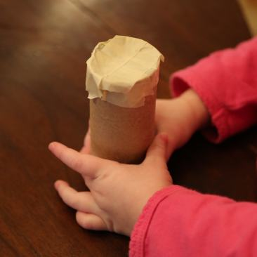 Child taping end of orzo shaker