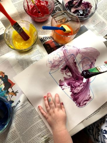 Child painting with purple egg yolk paint