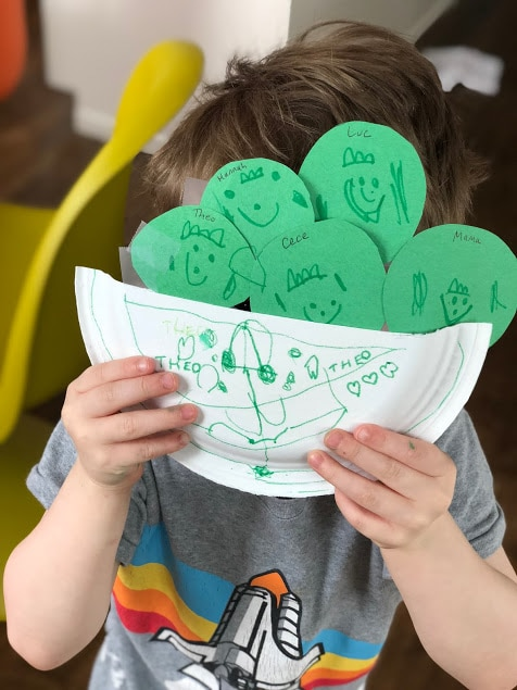 child holding our family Peas in a Pod Craft, with peas labelled as different members of the family
