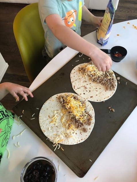 Child putting together quesadillas