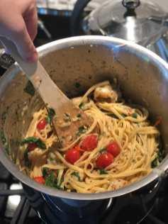 child stirring linguini and shrimp