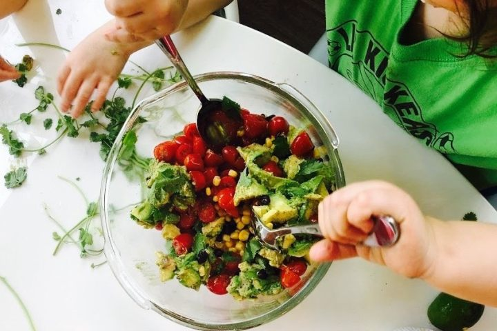 Child stirring avocado salad