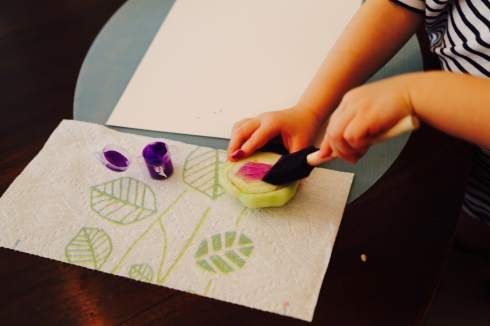 Child painting baby bok choy head
