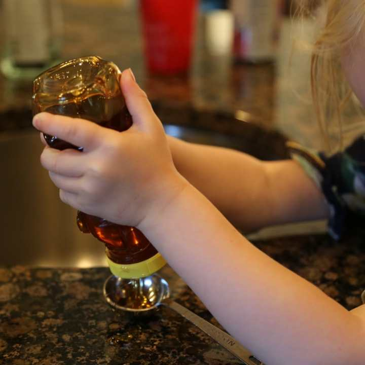 Child measuring honey
