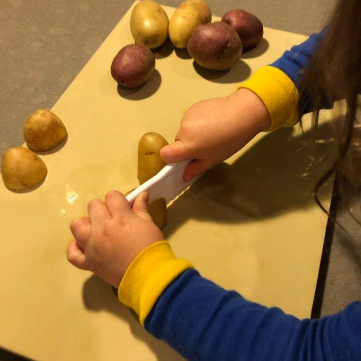 Child slicing potatoes