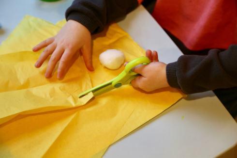 Child cutting yellow tissue paper