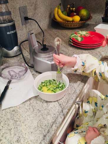Child mixing veggies into egg