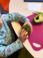 Child de-seeding green bell pepper