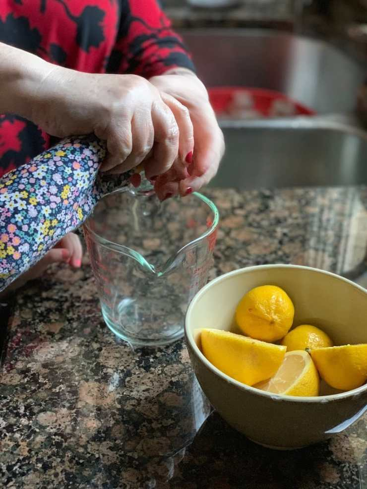 mom and child hands squeezing lemons into pyrex measuring cup