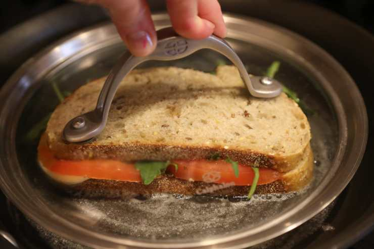 Child pressing down panini with a pan's lid as it cooks on stove
