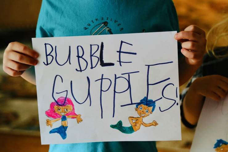 Child holding sign that says Bubble Guppies