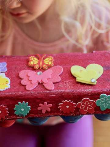 child holding egg carton treasure box