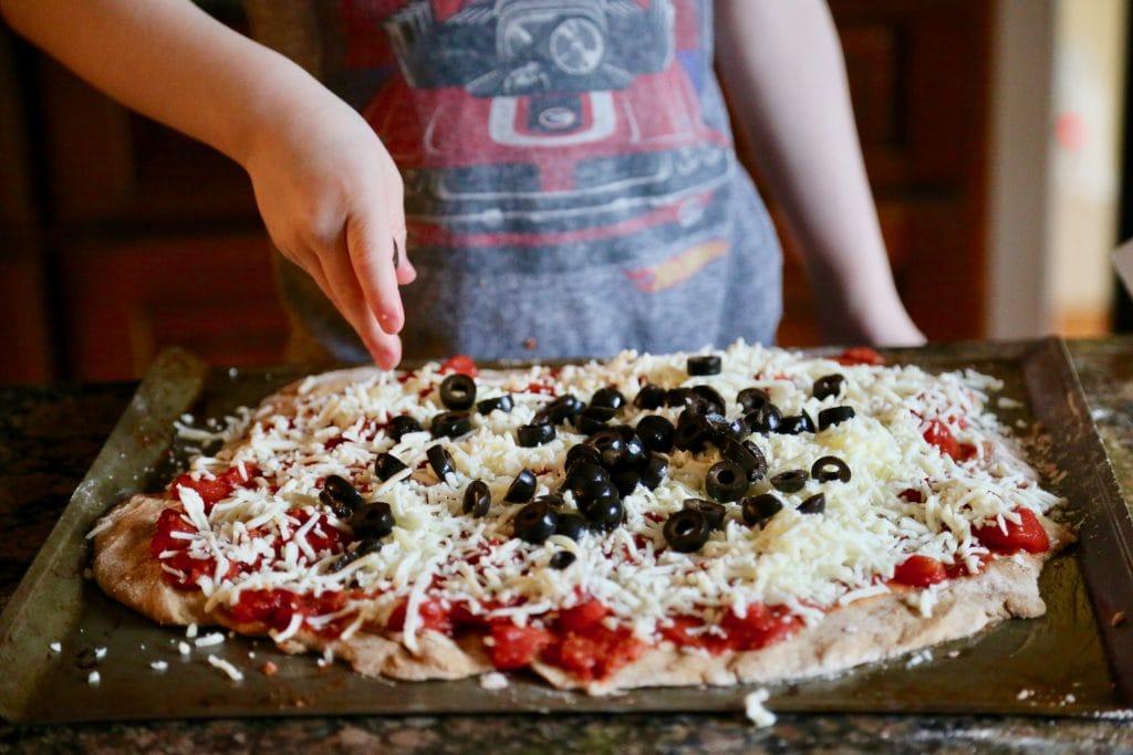 child placing black olives on pizza