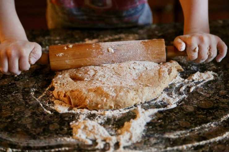 child rolling pizza dough