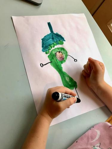 child drawing feet onto pepper