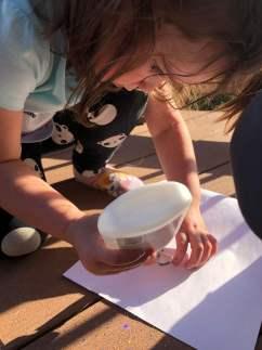 Child gluing pasta to paper