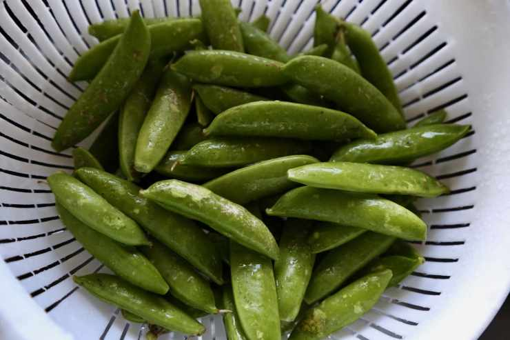 sugar snap peas in a strainer