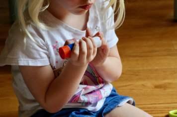child gluing chickens nose onto chicken napkin ring
