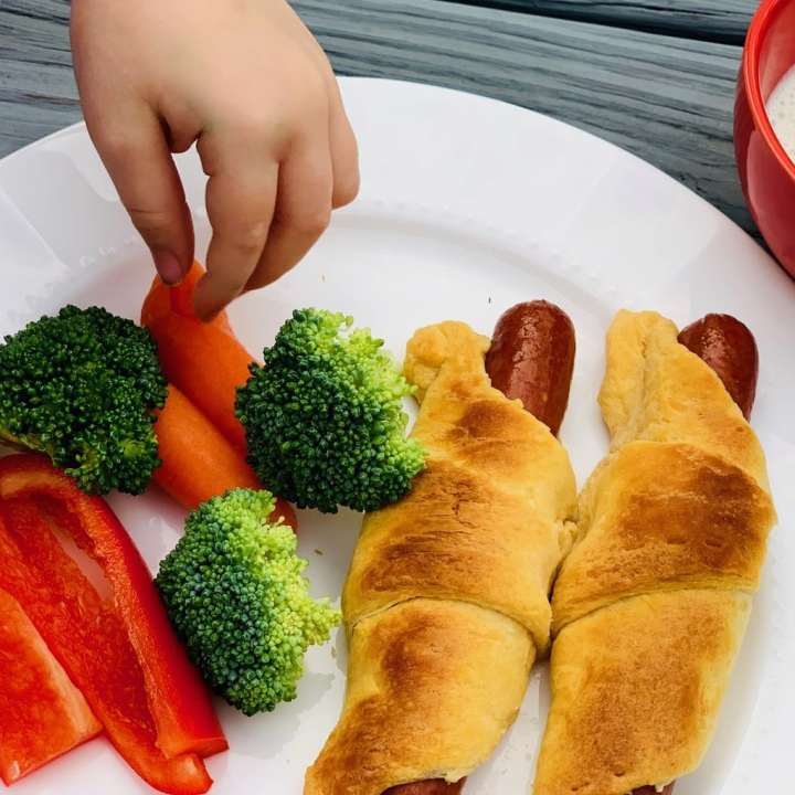 Crescent hot dog with veggies on plate