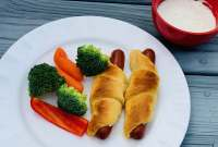 crescent dog on plate with broccoli, red peppers and carrots