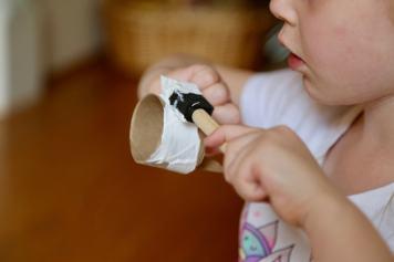 child painting chicken's head white