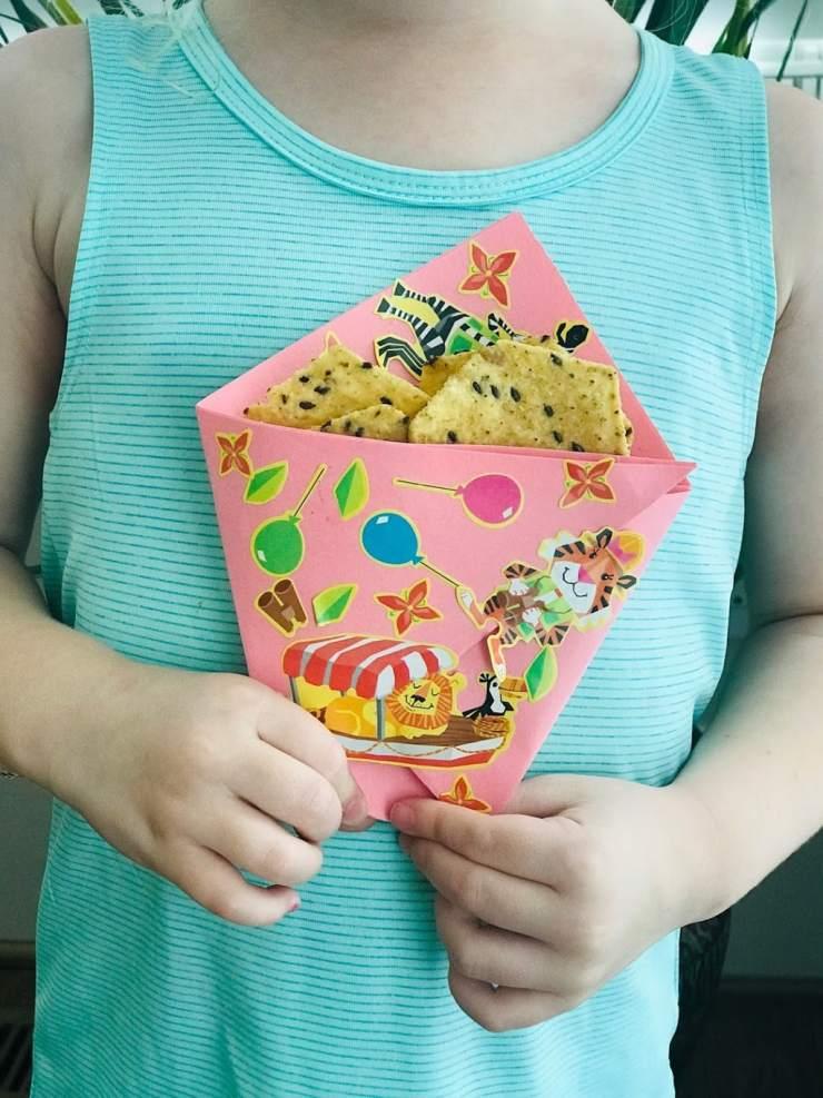 Child holding pink chip bag